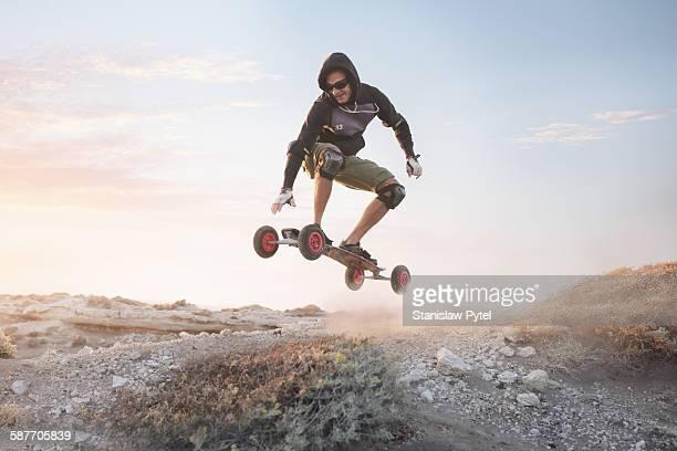 Man jumping on landboard at sunrise