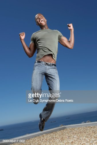 Man jumping on rooftop, smiling : Stock Photo