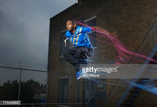 man jumping on rooftop with light trails