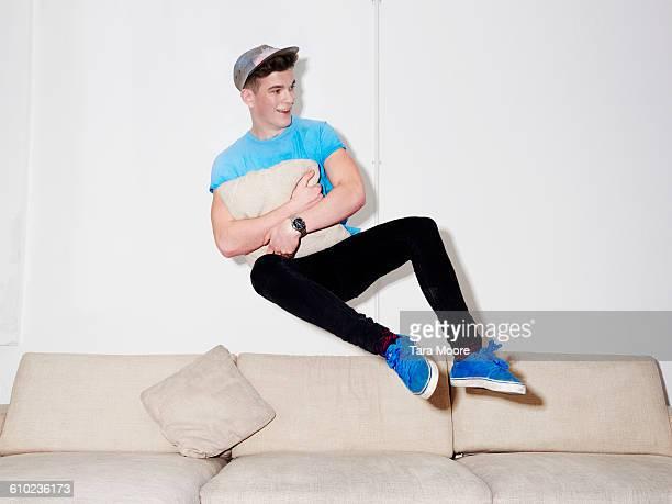 man jumping on sofa
