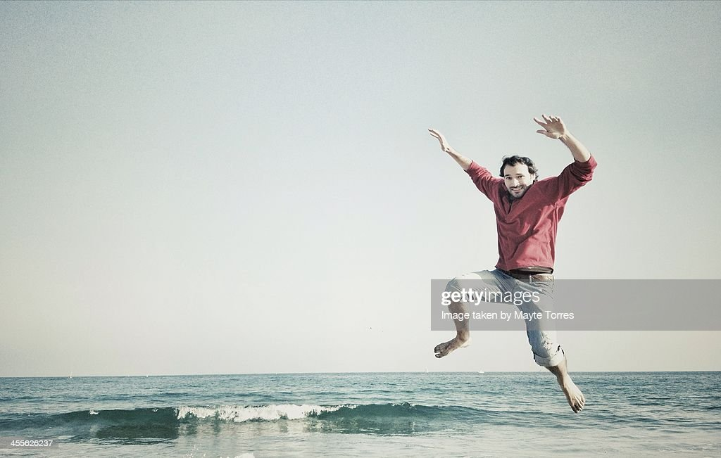 Man jumping on the beach in winter : Stock Photo