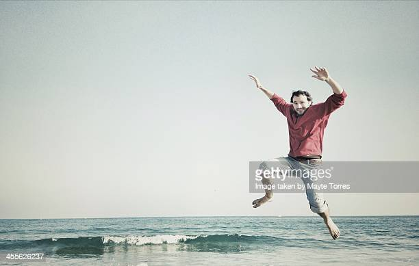 Man jumping on the beach in winter