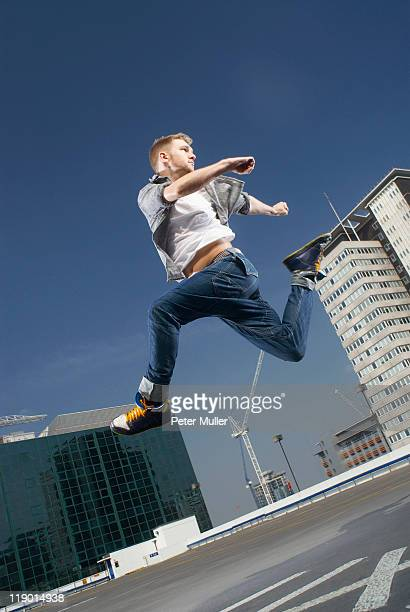 Man jumping on urban rooftop