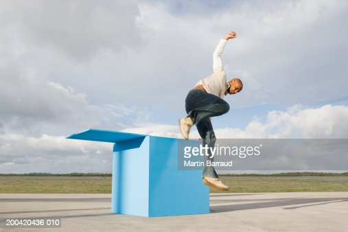Man jumping out of large blue box : Stock Photo