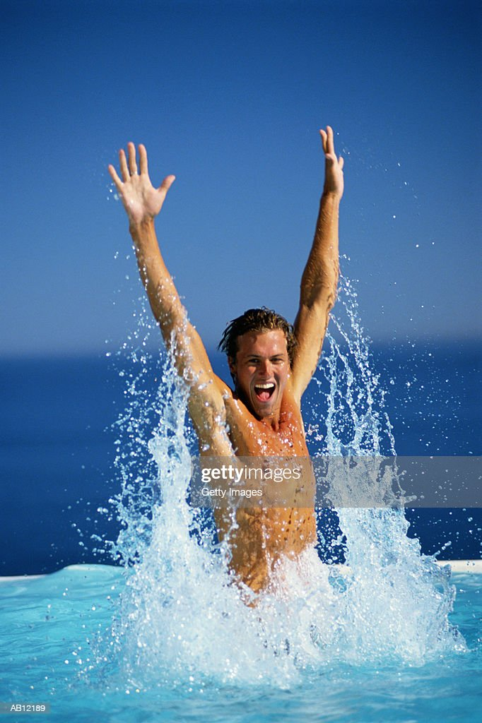 Man jumping out of water in swimming pool