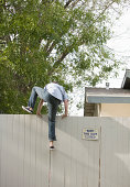 Man jumping over fence, rear view
