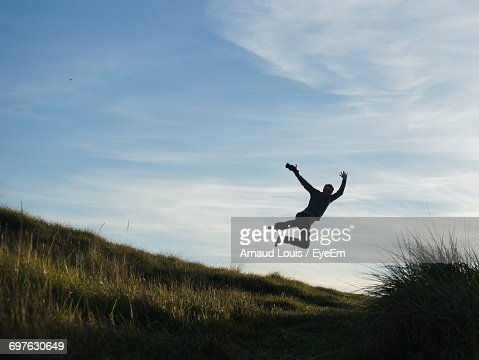Man Jumping Over Grassy Field Against Sky