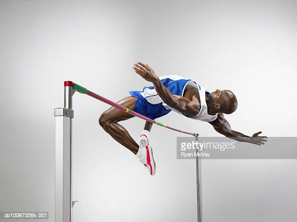 Man jumping over high jump, studio shot