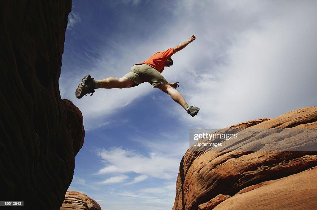 Man jumping over rock ledge
