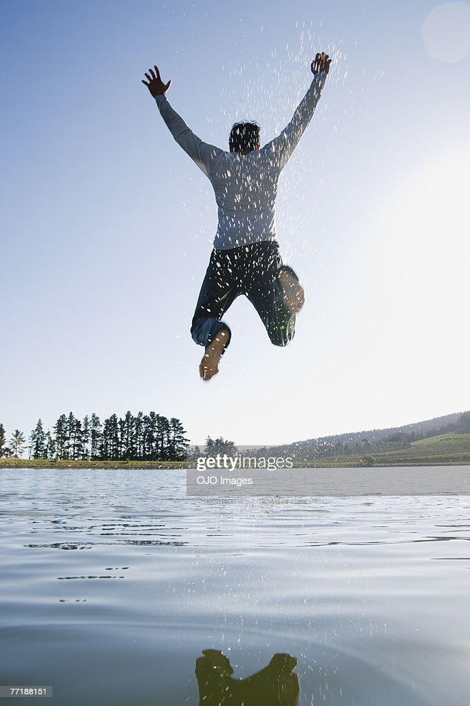 A man jumping overtop of water : Stock Photo