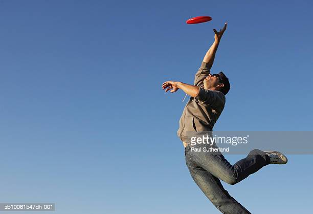 Man jumping to catch flying disc