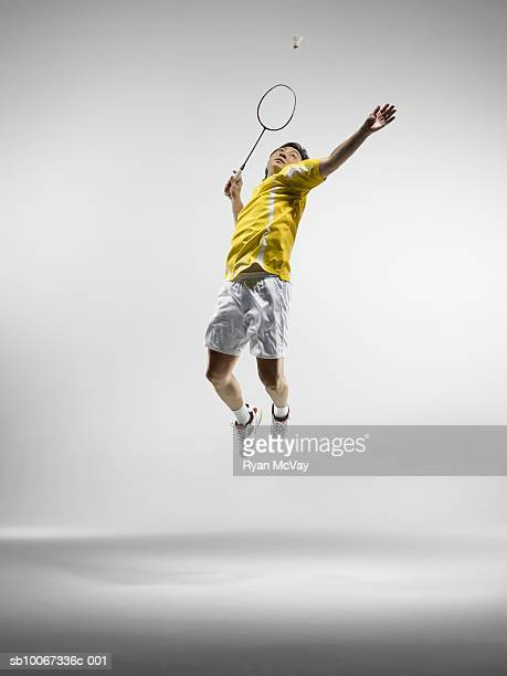 Man jumping to hit badminton birdie, studio shot