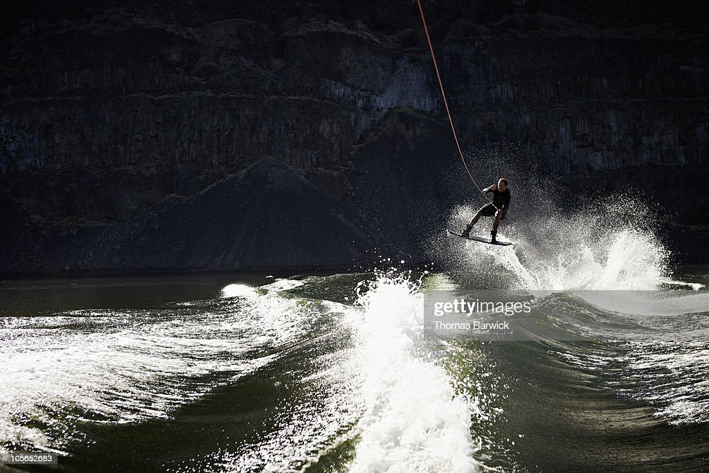 Man jumping wake in mid air on wakeboard : Stock Photo