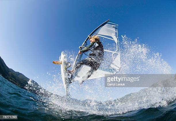 Man jumping wave on windsurf board, low angle view
