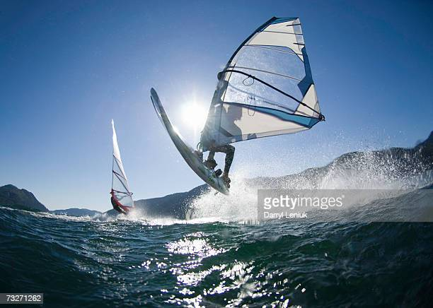 Man jumping wave on windsurf board, rear view