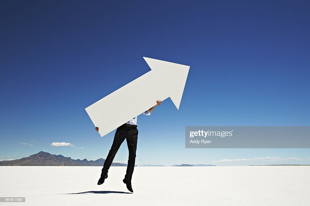 Man jumping with giant arrow in desert.