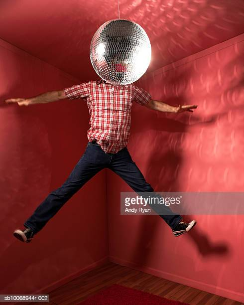 Man jumping with head behind disco ball