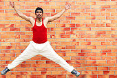 A man jumping with his back to a wall