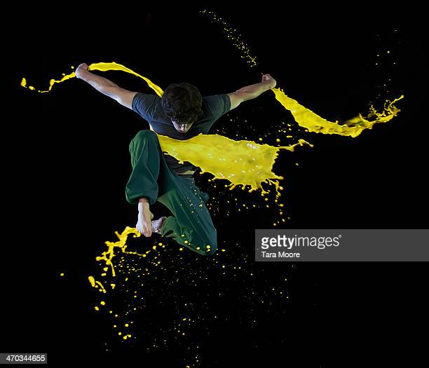 man jumping with paint splashes