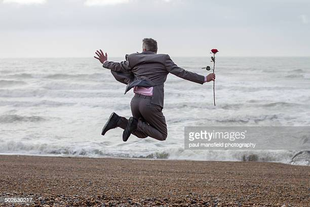 Man jumping with rose