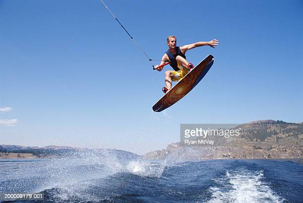 Man jumping with wakeboard in lake, view from below