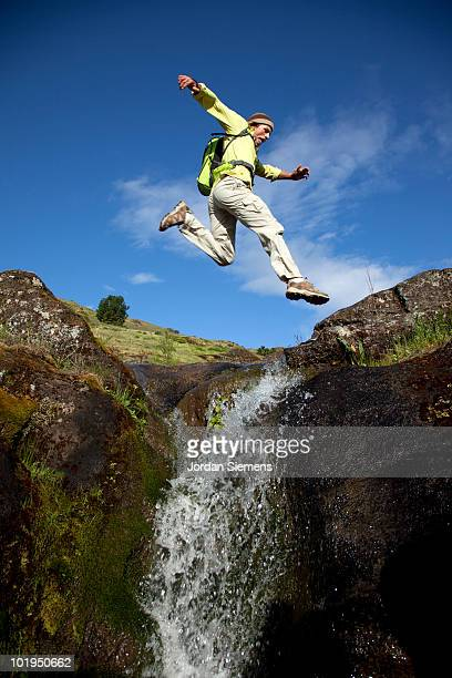 Man jumps across a waterfall while hiking.