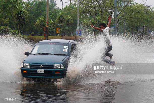 A man jumps away from water splashed from a passing car on a water logged street near Sector 41 in on July 7 2012 Noida India