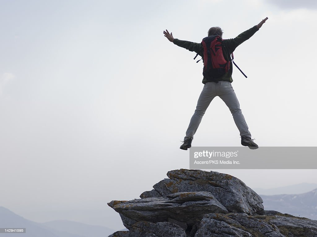 Man jumps for joy from rock summit, mtns below : Stock Photo