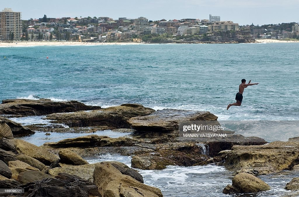 A man jumps into the sea to cool off at Manly beach in Sydney on January 8, 2013. Authorities warned New South Wales state faced one of the highest-risk fire days in its history, and temperatures rapidly climbed above 40 degrees Celsius (104 degrees Fahrenheit).