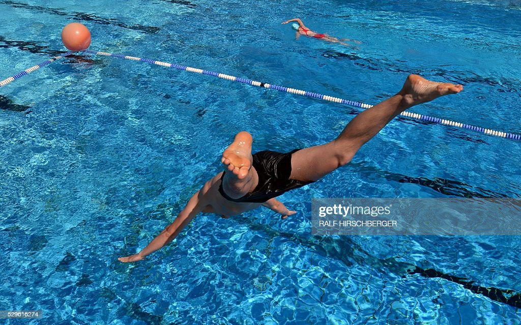 A man jumps into the water of the Freibad Kiebitzberge public open air swimming pool in Kleinmachnow near Potsdam northeastern Germany on May 9 2016...