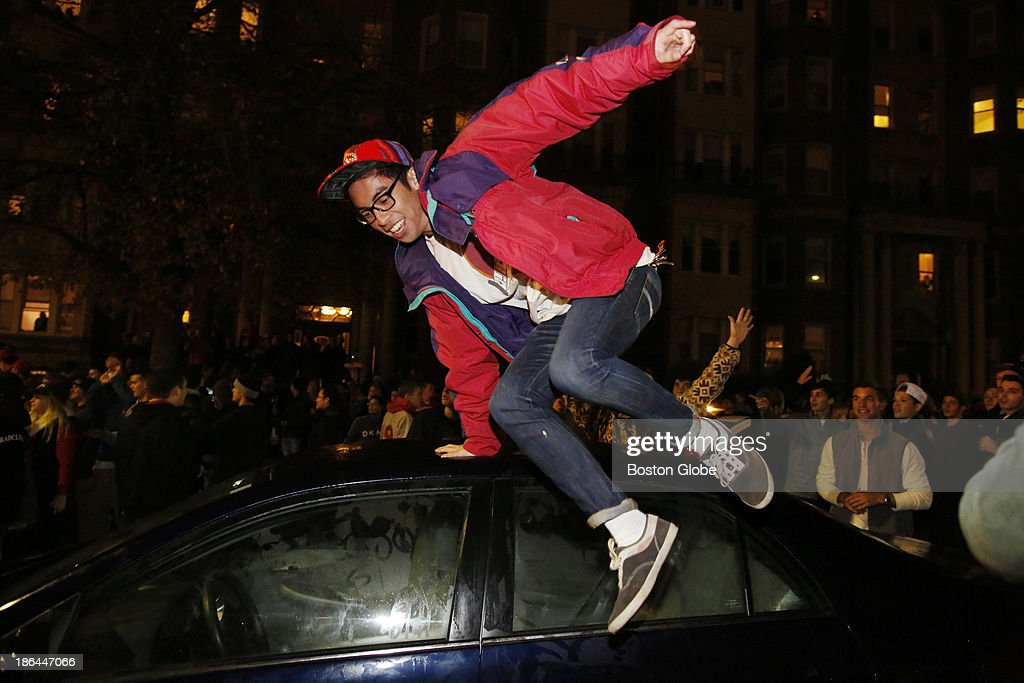 A man jumps off of a car as riot police move people back after celebrations got out of control outside of Fenway Park after the Red Sox won Game Six and the World Series at Fenway Park in Boston, Oct. 31, 2013.