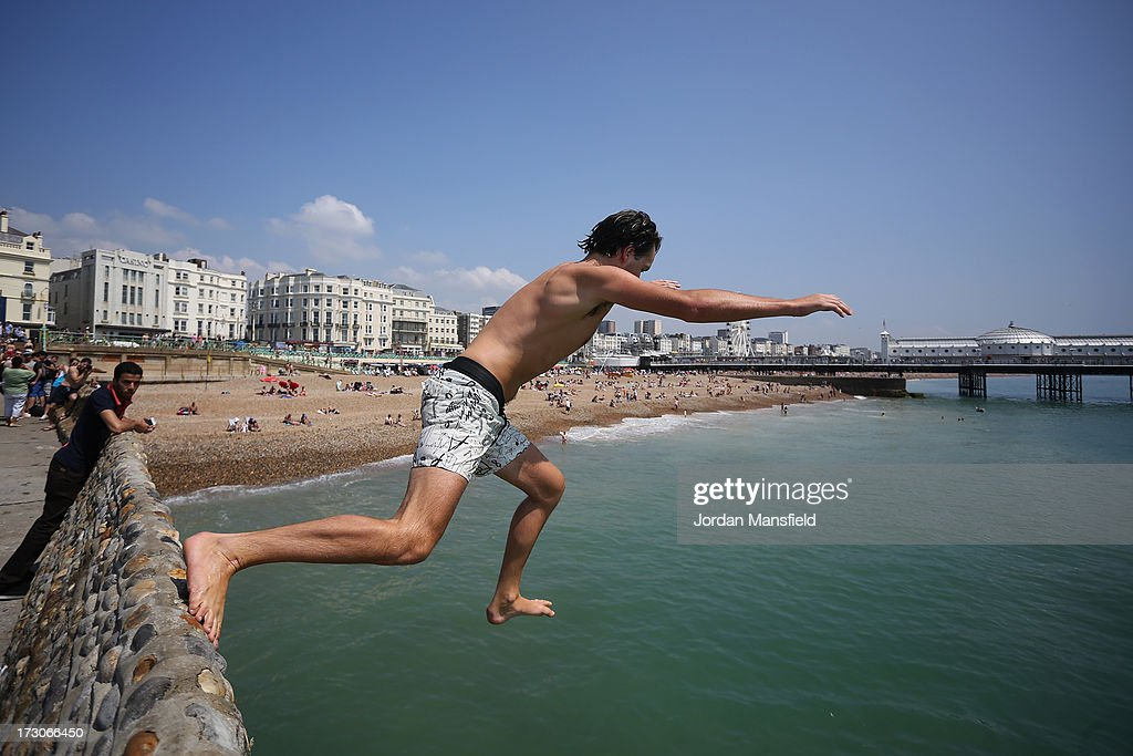 A man jumps off the a wall into the sea on July 6, 2013 in Brighton, England. Many people are expected to flood to the British seaside as the country enjoys a heatwave.