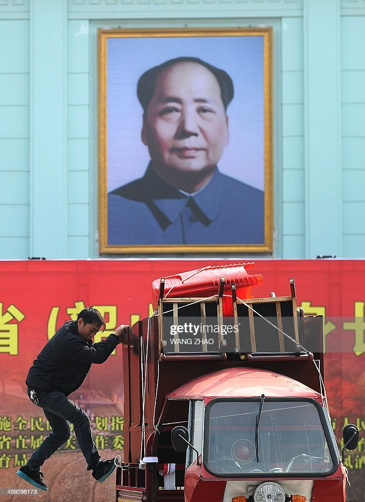 A man jumps out of a motor tricycle after packing chairs and desks in front of a portrait of former Chinese leader Mao Zedong in Shaoshan, in China's central province of Hunan on December 25, 2013. Thousands of admirers of Communist China's founder Mao Zedong flocked to his home town on December 25 to bow before his graven image -- including one statue of solid gold -- before the 120th anniversary of his birth.