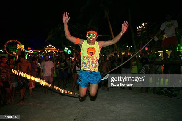 A man jumps over a burning rope at the full moon party on the beach of Haad Rin on August 22 2013 on Koh Phangan Thailand Thousands of people from...