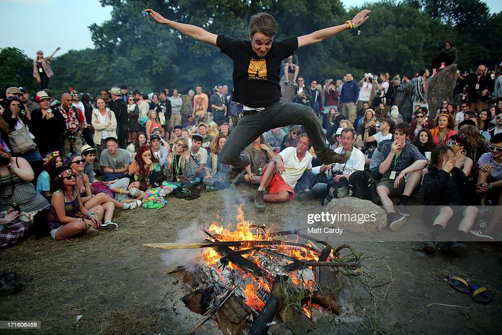 A man jumps over a fire that has been lit inside the stone circle as people gather for sunset at the Glastonbury Festival of Contemporary Performing Arts site at Worthy Farm, Pilton on June 26, 2013 near Glastonbury, England. Gates opened on Wednesday at the Somerset diary farm that will be playing host to one of the largest music festivals in the world and this year features headline acts Artic Monkeys, Mumford and Sons and the Rolling Stones. Tickets to the event which is now in its 43rd year sold out in minutes and that was before any of the headline acts had been confirmed. The festival, which started in 1970 when several hundred hippies paid 1 GBP to watch Marc Bolan, now attracts more than 175,000 people over five days.