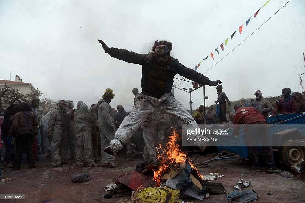 A man jumps over fire as people celebrate the annual custom of Flour War in Galaxidi, some 250kms south east of Athens on March 18, 2013.
