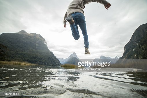 Man jumps over mountain river : Stock-Foto