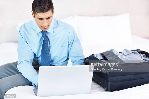 Man just arrived to hotel room and working on laptop