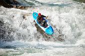 Man kayaking off waterfall in white water rapids