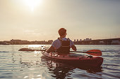 Handsome sporty man is kayaking on sunset. Canoeing alone.