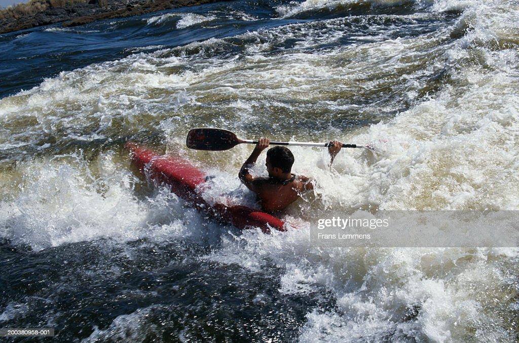 Man kayaking, rear view