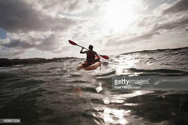 A man kayaks in the ocean