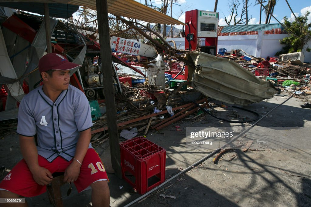 A man keeps guard outside a destroyed gas station in Tacloban, the Philippines, on Monday, Nov. 18, 2013. Super Typhoon Haiyan slammed into the central Philippines on Nov. 8, knocking down most buildings, killing thousands, displacing 4 million people and affecting more than 10 million. Photographer: Paula Bronstein/Bloomberg via Getty Images