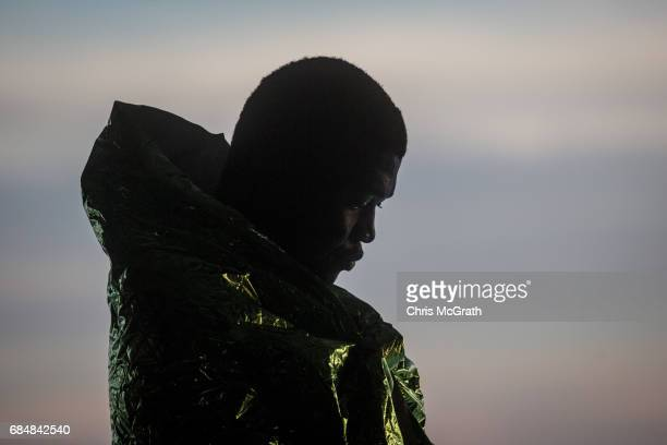 A man keeps warm under a blanket on board the Migrant Offshore Aid Station Phoenix vessel after being rescued at sea on May 18 2017 in the Lampedusa...