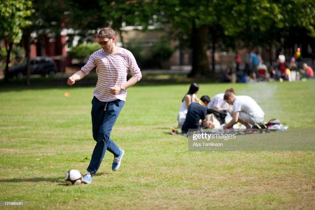 Man Kicking a Football in a City Park : Stock Photo