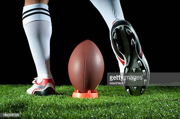 Man kicking an American football