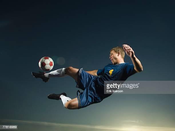 Man kicking soccer ball in air
