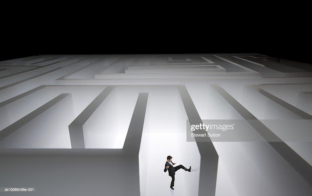 Man kicking wall of giant maze : Stock Photo