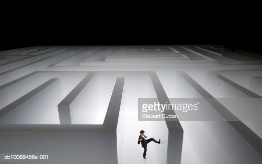 Man kicking wall of giant maze