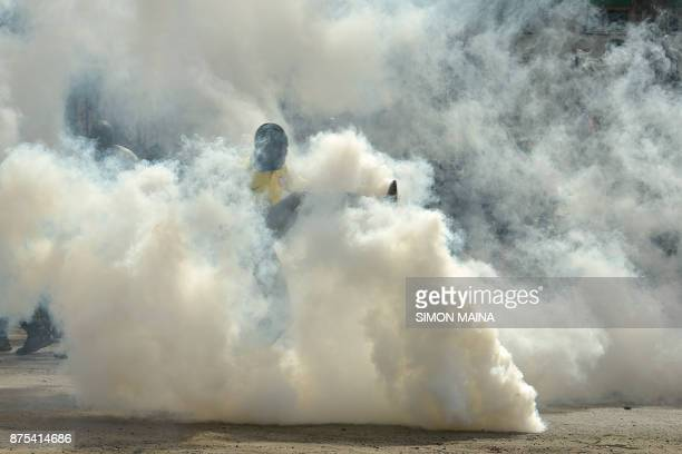 A man kicks a canister of tear gas as supporters of Kenya's opposition party National Super Alliance clash with police during a demonstration on...